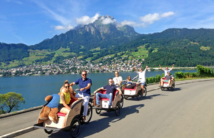 four cargo bikes riding along a lake with mountains in the background