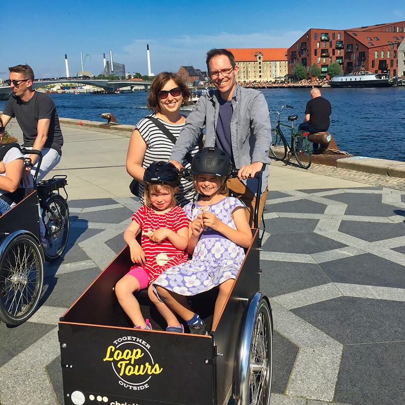 parents and 2 daughters smiling on cargo bike