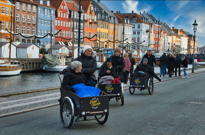 three cargo bikes taking a turn with their guests with blankets and colorful houses in the background