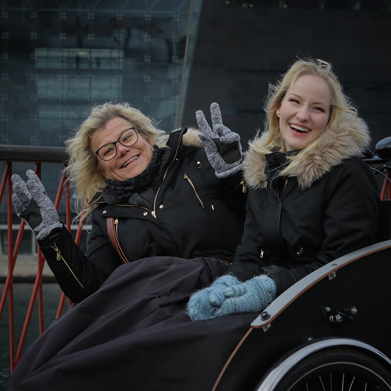 two women smiling at the camera from cargo bikes