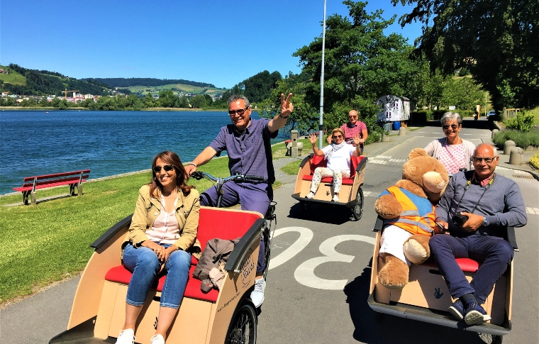 three tourists and one teddy bear on a bike tour next to a lake